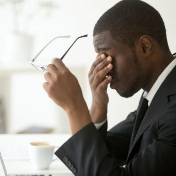 Tired of computer african businessman taking off glasses feeling