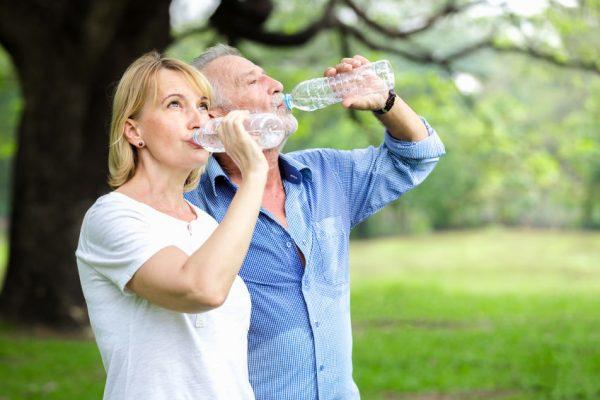 Senior couple standing drinking water