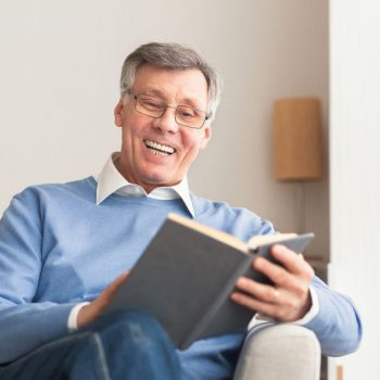 Senior Man Reading Book Sitting On Sofa At Home