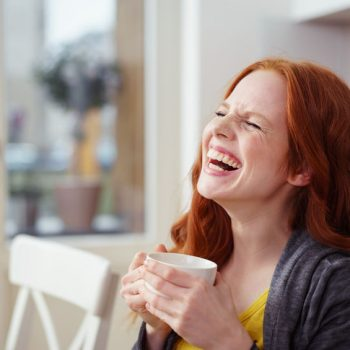 Spontaneous young woman enjoying a good laugh
